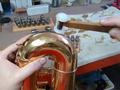 Abolladuras en el curvo de la campana de un saxofón