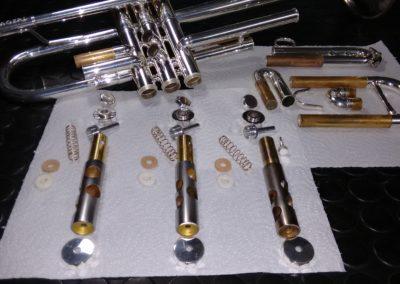 Carcasa y pistón de trompeta dañados con surcos y marcas de arañazos